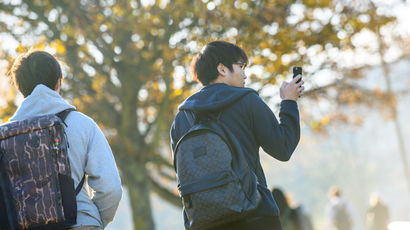 Two students on campus, one with a phone in his hand