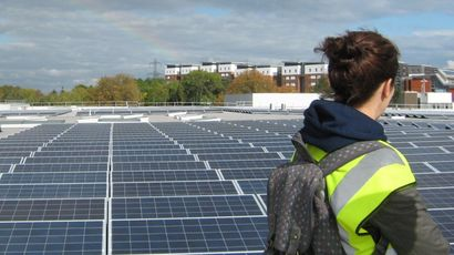 Student doing a masters in sustainability looks at the solar panels on campus