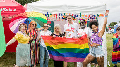 UWE Bristol staff members standing in front of a rainbow flag at Bristol Pride.