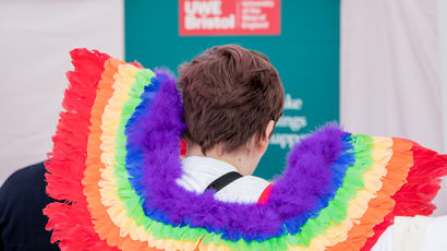 Closeup of someone wearing rainbow wings at Bristol Pride.