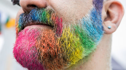 Closeup of someone's beard painted in rainbow colours at Bristol Pride.