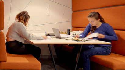 Two students sitting in a booth in the Maths Hub.