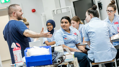 Nursing students being taught by a lecturer on a ward.