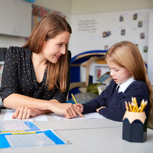 A female teacher with a young student, who is writing on a sheet of paper
