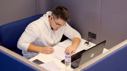 Student with a laptop working in a study booth.