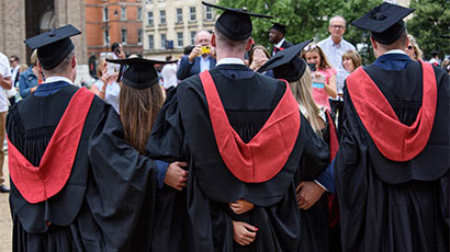 A photograph taken from behind of four students at graduation