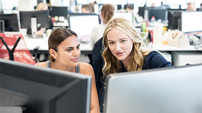 Two women working together on computers