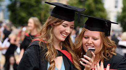 Two graduates at graduation looking at a phone