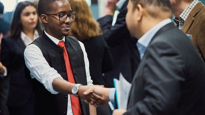 A student and visitor shaking hands at the Dragons' Den event, with a small crowd in the background.