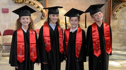 Four primary school aged children standing in a row, dressed in graduation gowns and wearing mortar boards.