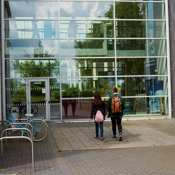 Two students walking towards a University building