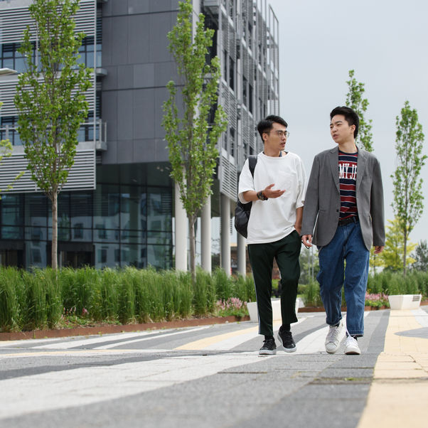 Two students walking past a University building