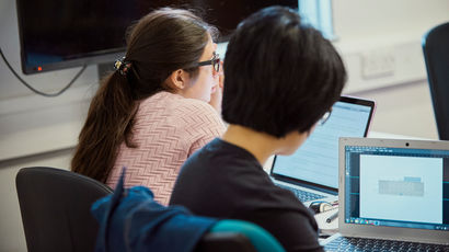 A back to camera shot of two female students working on laptops.
