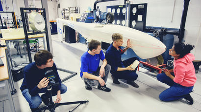 Group of male and female students looking at the bodywork of a glider in the workshop with the tutor.