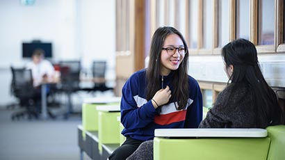Two international students talking in a study area