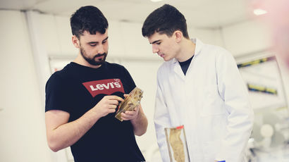 Two healthcare students analysing a specimen in a lab.