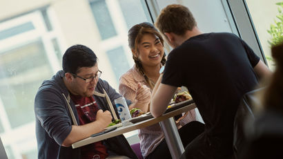 A group of students laughing around a table in OneZone.