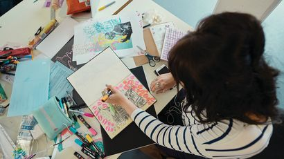 An illustration student working with pen and paper