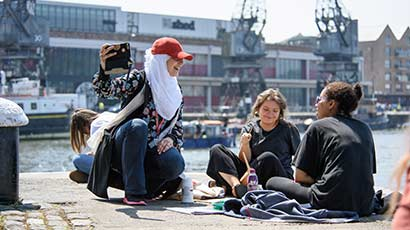 A group of students sat around some art materials by Bristol harbourside.