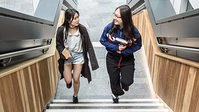 Two international students walking up some stairs in the Business School, chatting to each other.