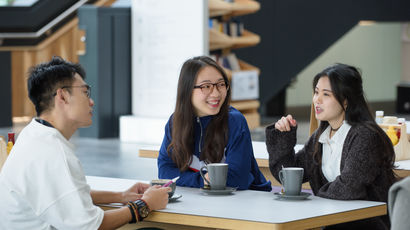 Three international students sitting at table in the Business school, having coffee and chatting to each other.