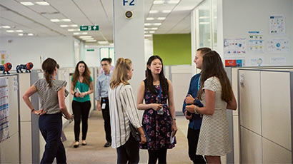 A group of UWE Bristol placements students chatting in an office setting