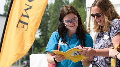 Two people reading an Open Day programme