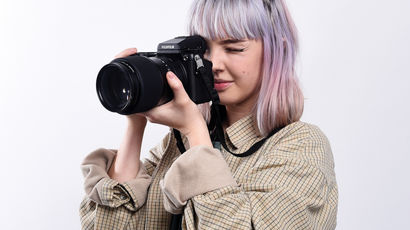 A student looking through the lens of a large camera