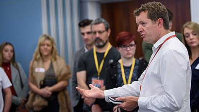 Prospective students listening to an academic at a Postgraduate Open Event
