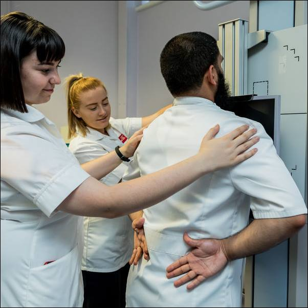 Uniformed students using radiotherapy equipment.