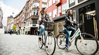 Two females cycling through Copenhagen city centre