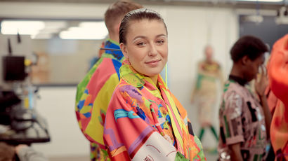 A fashion student looking directly at the camera, wearing a bright outfit