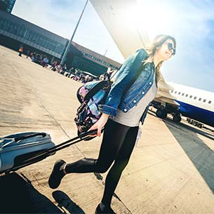 Woman pulling a suitcase across the tarmac next to a plane