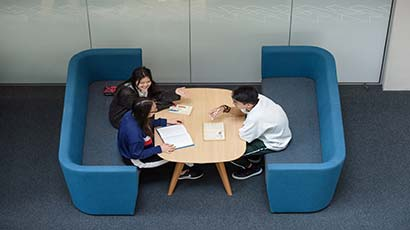 Three students sat on sofas working together across a table
