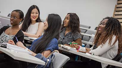 Group of students in a lecture, with books, pens and laptops, all are wearing smiles and interacting with the off screen lecturer.