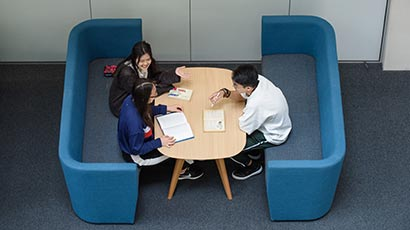 Three international students sitting in the Business School, working