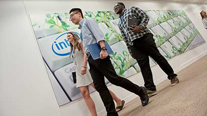 Three smiling placement students walking down the corridor at the Intel office as they hold netbooks under their arms.