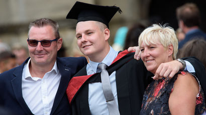 Graduand posing with family outside Bristol Cathedral.