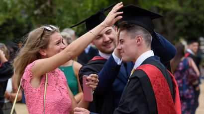 Graduand's relative adjusting their cap on College Green.