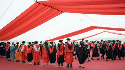 Graduands and academic staff wearing robes in a marquee for an Awards Ceremony.