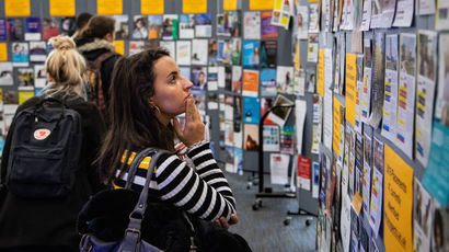 A female student browses a stand at the employer fair