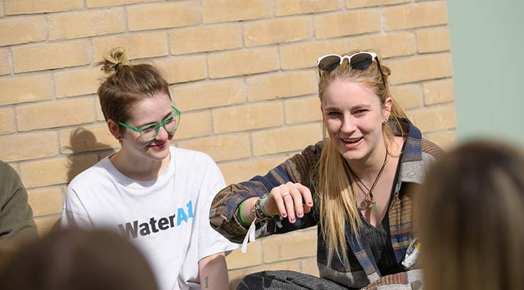 Two students chatting outside student accommodation in the sun