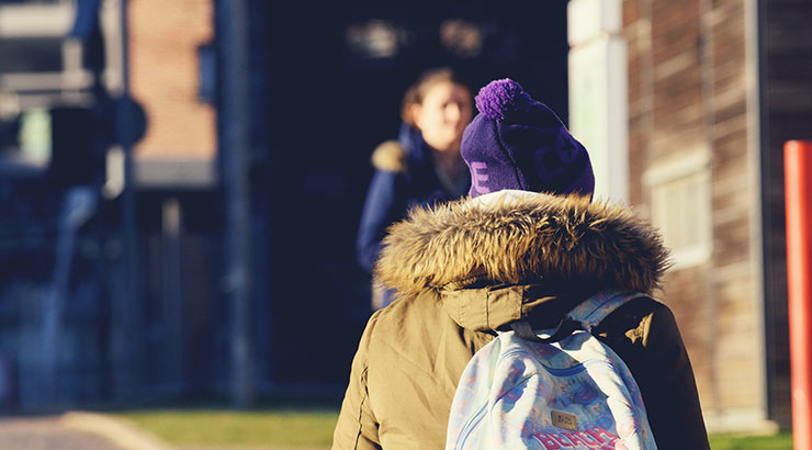 Student walking outside in the winter sun