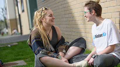 Two students sitting outside accommodation