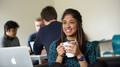 A student holding a coffee cup and smiling