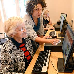 A volunteer helping an elderly woman to use a computer.