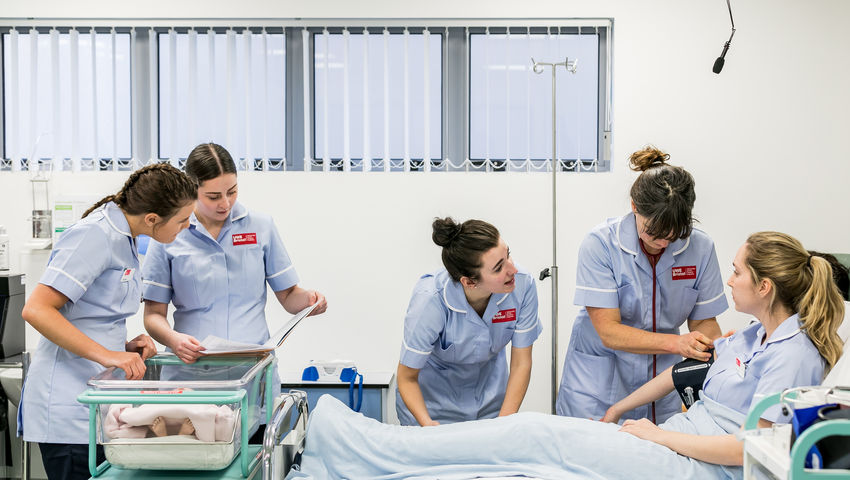Midwifery students with a dummy in the Skills Simulation Suite on Glenside Campus.