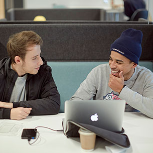 Two students talking whilst using a laptop