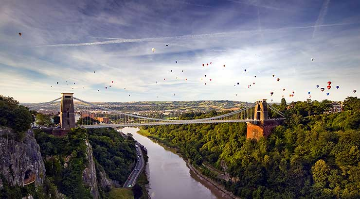 Aerial view of the Bristol Suspension Bridge with hot air balloons