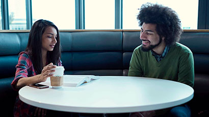 Two students having a conversation in a booth on campus